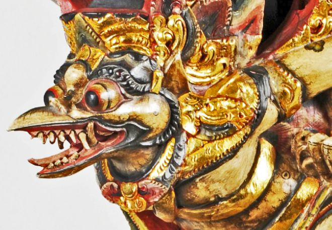 Close-up of the face, showing bulging eyes, beak open with lots of teeth and tongue.  The statue is gold leafed and painted red and black.