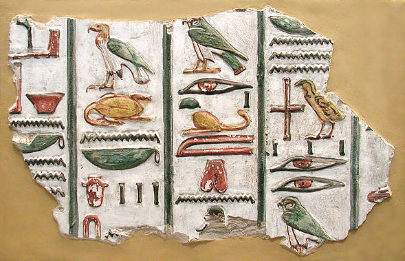 Colour photograph showing vertical columns of hieroglyphs painted in green, yellow and red.