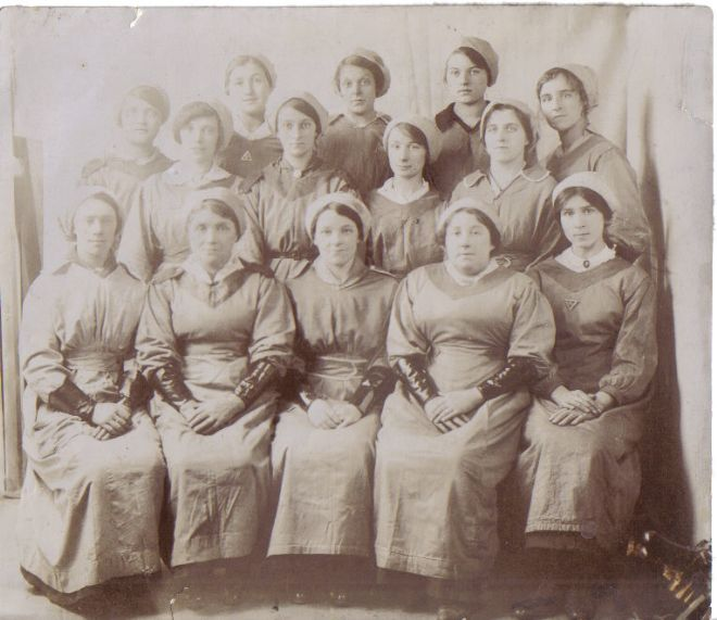 Group photograph of female factory workers.  they are wearing leather (?) gauntlets for protection.