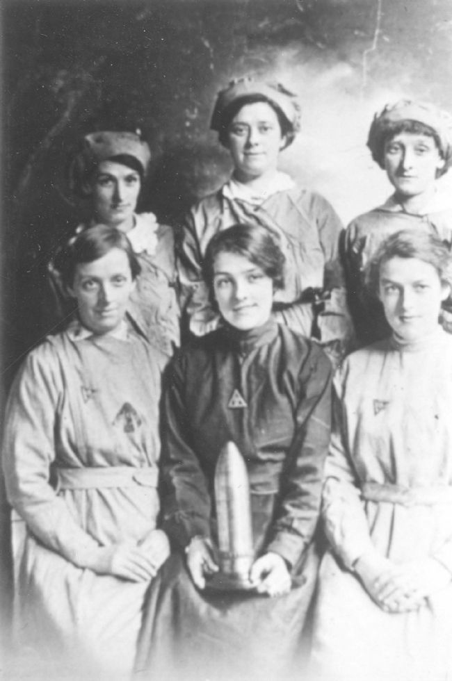 Black and white photograph of six female factory workers. The girl in the front, centre, is holding a shell case.