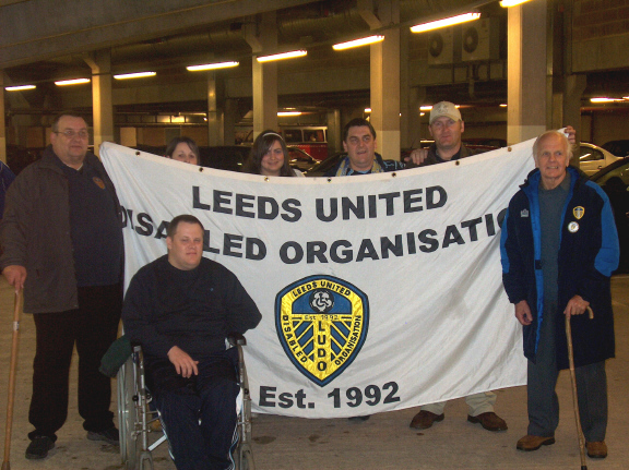 Colour photograph showing a group of people holding a flag which has Leeds United Disabled Organisation printed on it.