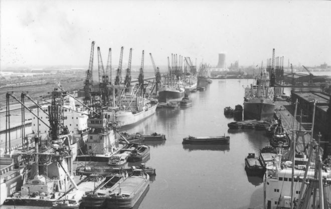 Black and white photograph of Hull's docks, with boats and barges docked and many cranes