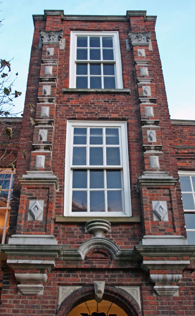 the house is made of red brick, with stoen carvings.  It is three stories high with large sash windows.