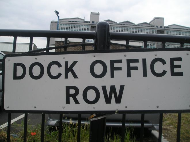 Black and white street sign with the words 'Dock Office Row'