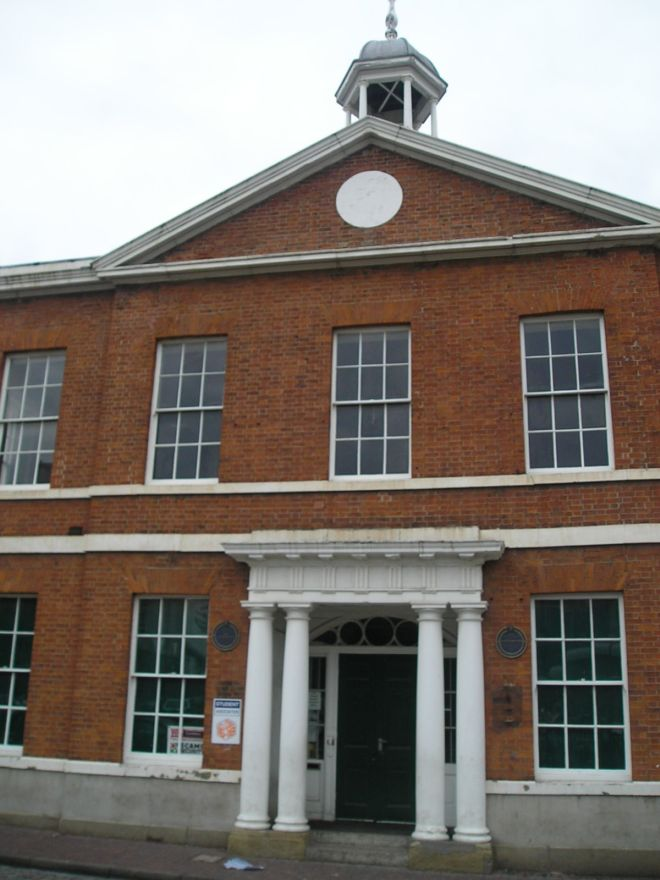 Red brick building with a central doorway flanked by pillars