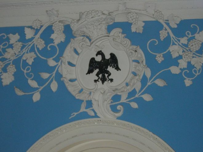 Close-up photograph showing a blue wall with white plasterwork of a grape vine and an eagle.  The eagle is painted black.