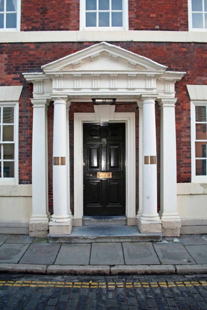 Close up photo of the front of a grand red brick house.  The doorway is flanked by white painted pillars.