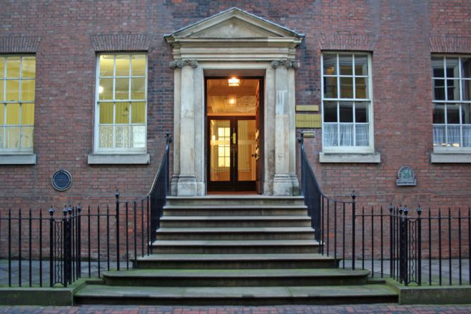 Entranceway of a house showing steps up to a grand front door.  Either side are large sash windows.