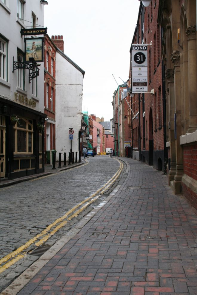 View down Hull high street showing a narrow cobbled road lined with buildings on each side.