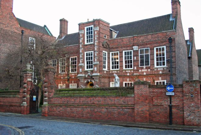 Red brick house with sa chimney at each end and large sash windows along the length.