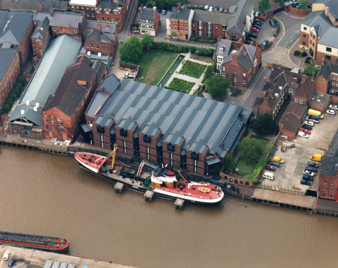 Photograph shows the water, with a boat moored next to old warehouses.