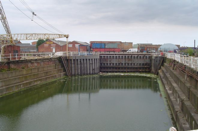 Photograph shows an area of water surrounded by brick walls.  On the side is a crane.