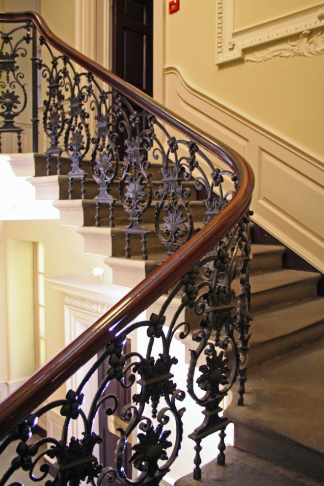 Stone staircase with beautiful wrought iron balustrade in the shape of flowers and other designs.