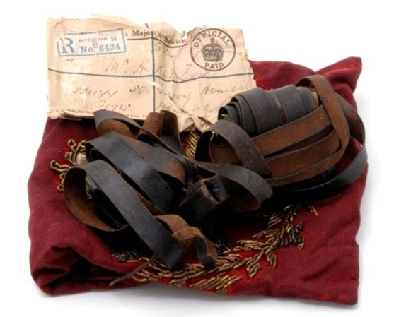 Small leather pouch with long leather straps on  a dark red piece of material.