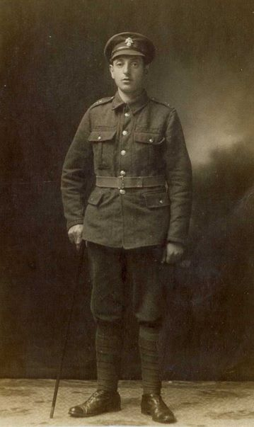 Black and white photo showing Hyman in WW1 uniform.  He wears a peaked cap and is standing up straight  with a cane in his right hand.