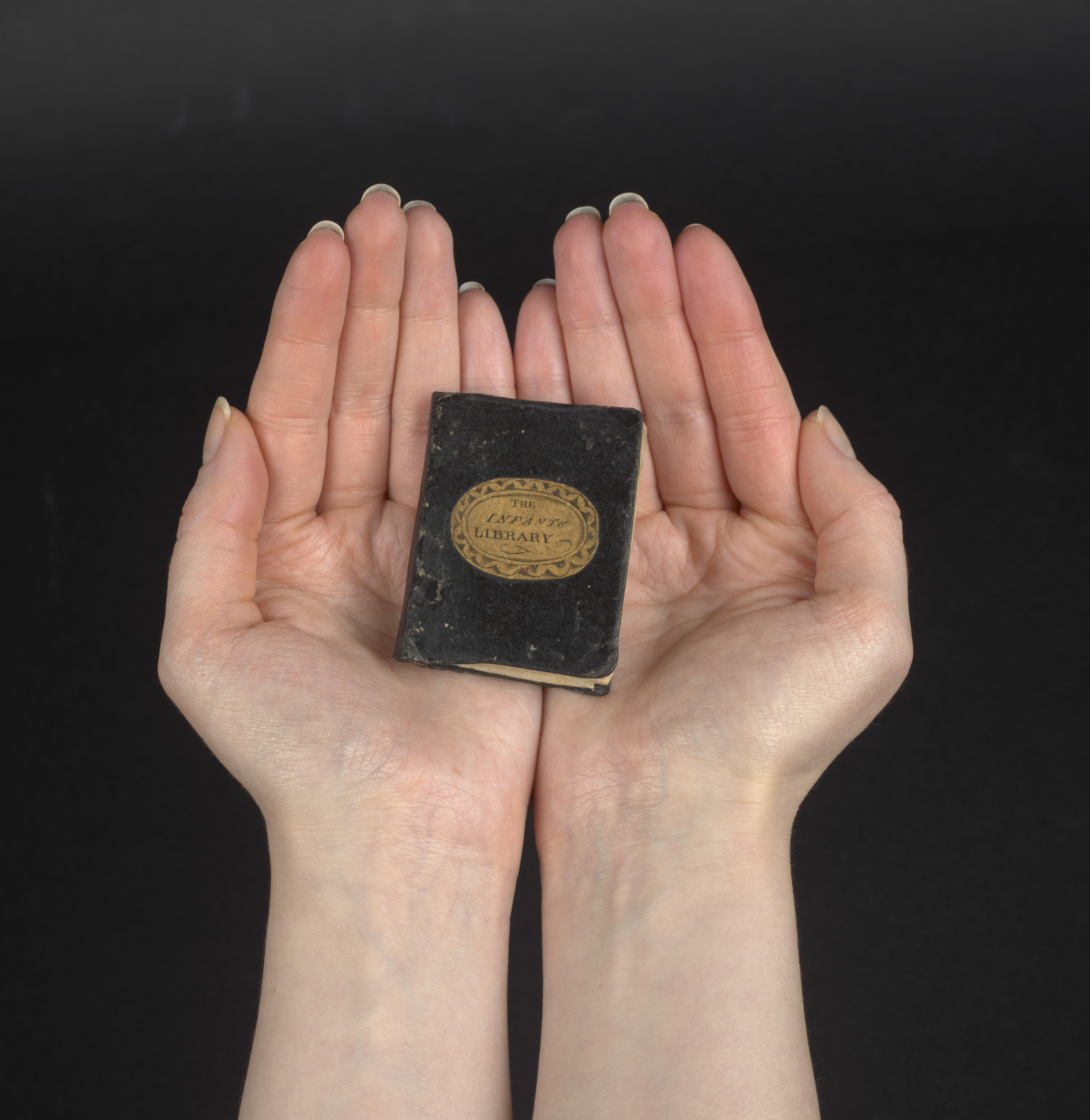 An adult's hand with a mini book in the palm. The book only covers about half of the palm.