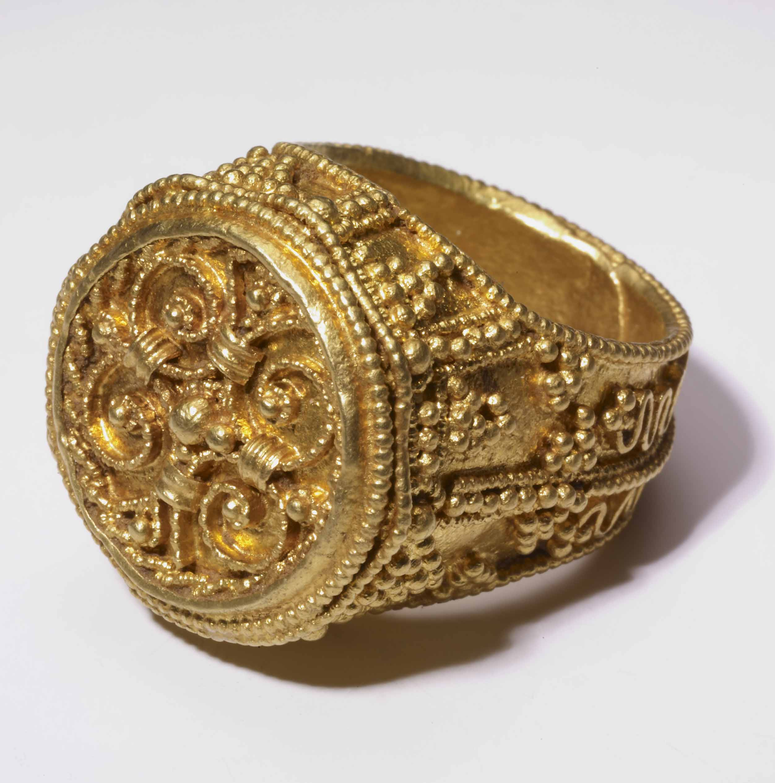 Medieval gold ring with circular face and detailed filigree design.
