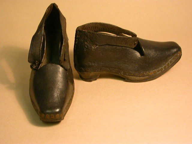 Small pair of dark brown leather clogs with wooden soles.  The leather uppers are attached to the sole using metal tacks.