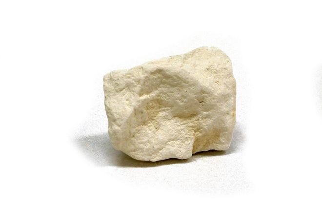 Piece of chalk, white in colour with smoothed angles