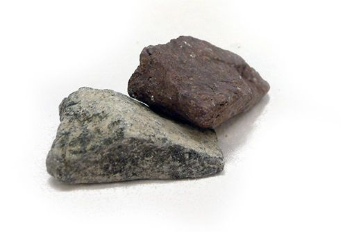 Two pieces of limestone, one a darker grey than the other.  One is much more mottled, dark and light grey.