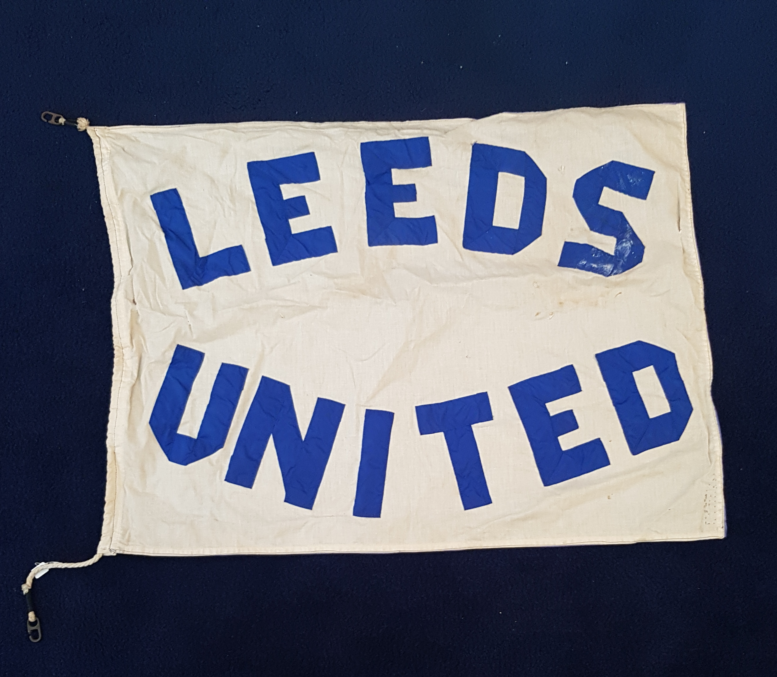 White flag with blue lettering that says 'Leeds United'