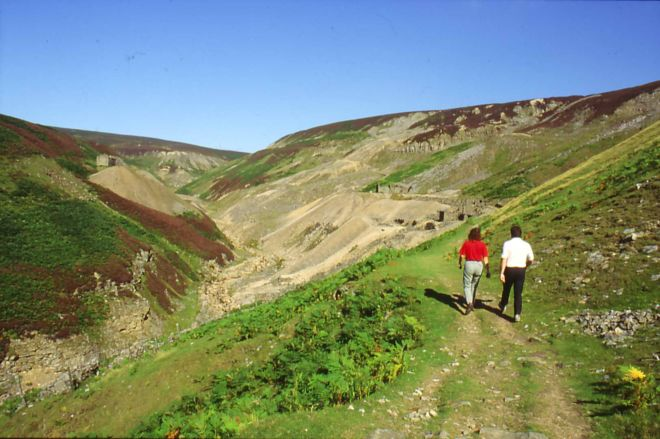 Walkers enjoying a stroll up a moorland valley.  They are walking along a ridge, with a valley to their left.