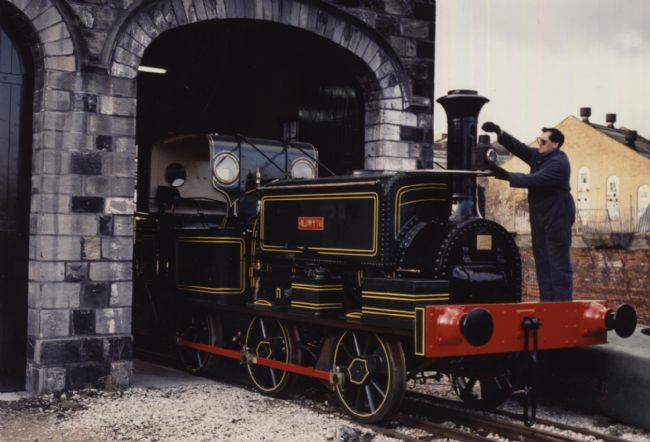 Aldwyth in her original chocolate coloured paint with a red fender.  The engine is coming through a tunnel and there is a man standing on the front of the engine.