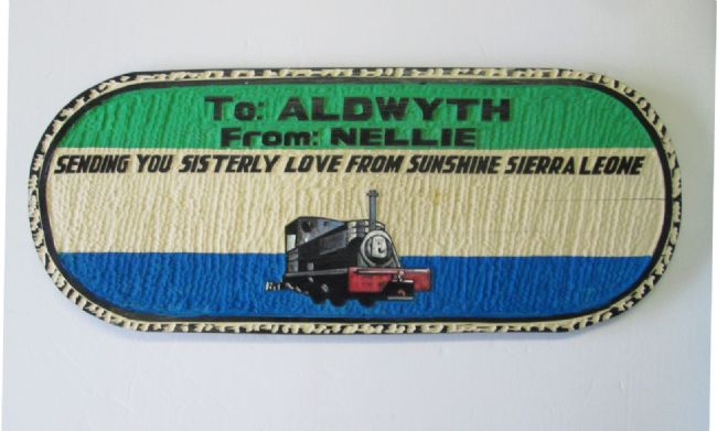 """Plaque reads:  """"To Aldwyth from Nellie.  Sending you sisterly love from sunshine Sierra Leone"""".  There is a small picture of Nellie underneath."""