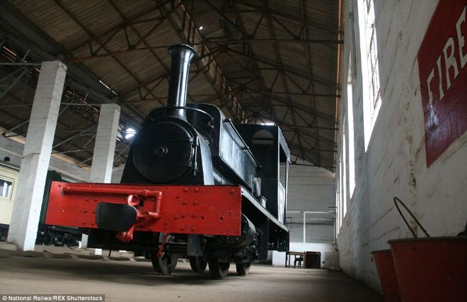 Nellie in a large engine shed.  She has been fully restored and has a red fender.