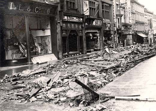 Black and white photograph showing bombed out shops.  All the windows have been blasted out and the steet is full of debris.