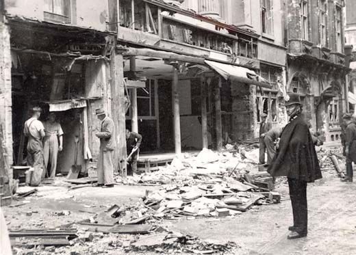 Black and white photograph showing part of a bombed out stret.  There is a policeman standing in the bottom right of the photo.  Workers are in one of the bombed out shops.