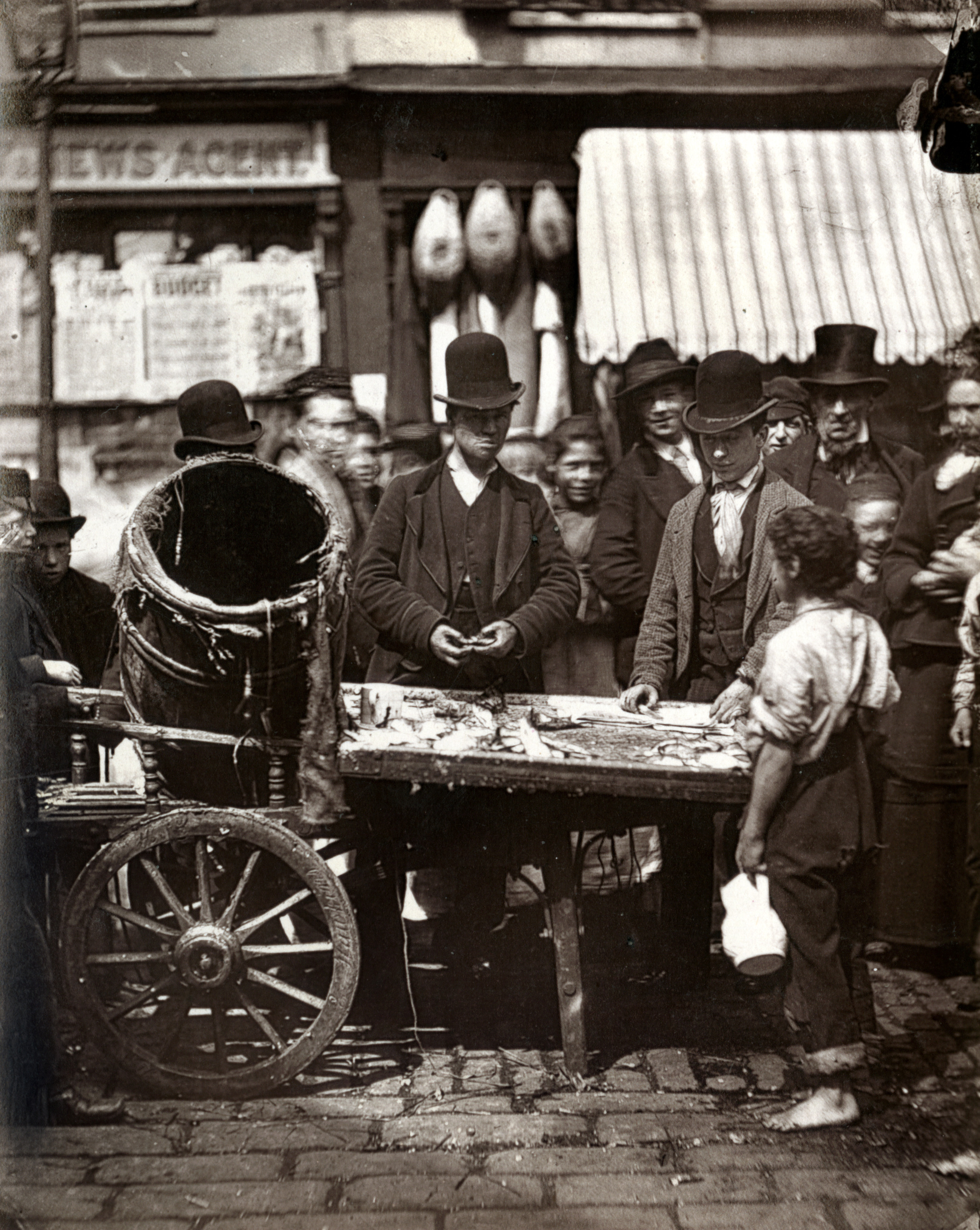 Black and white image of men wearing bowler type hats around a barrow selling fish. There's a boy in the foreground.