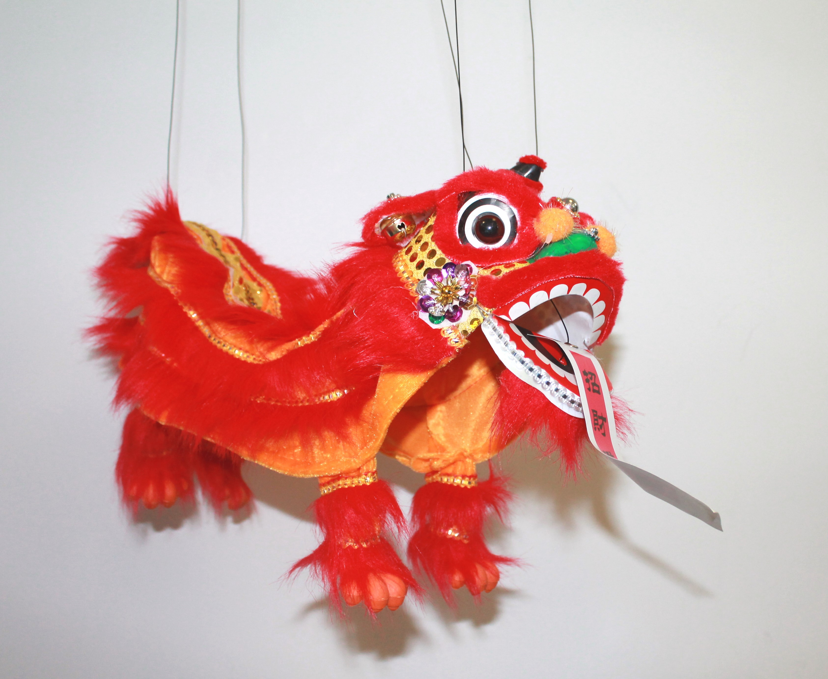 Orange and red lion puppet on strings.
