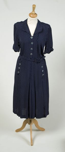 A mid-length short sleeved dress in navy blue with white dots