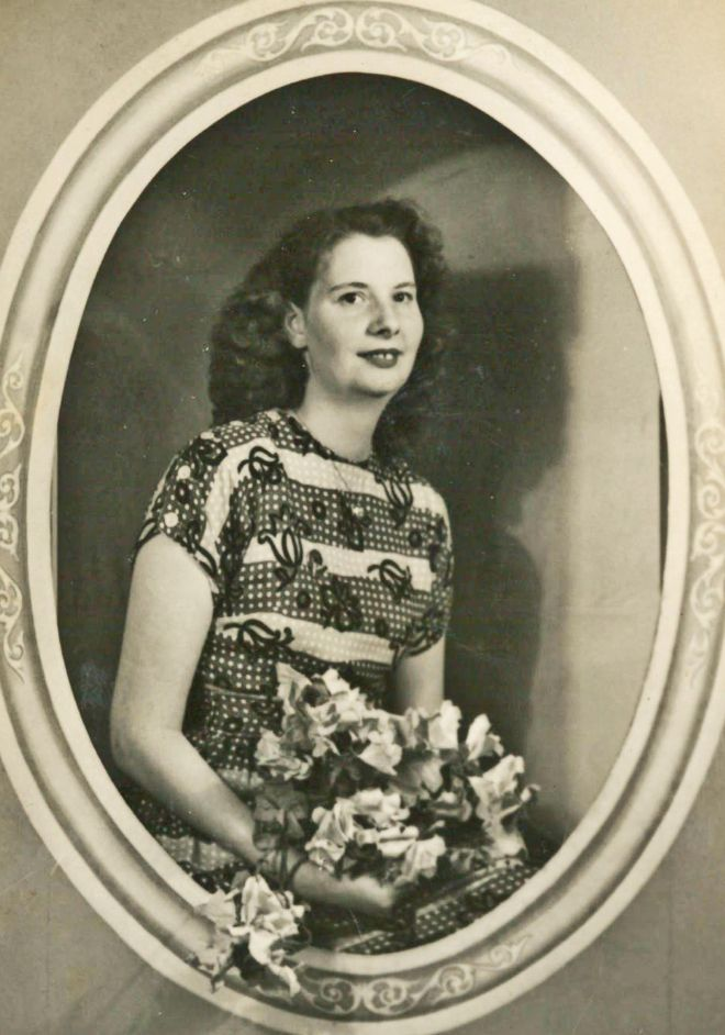 Black and white portrait photo of a woman holding a bunch of flowers and wearing a stripy M&S dress