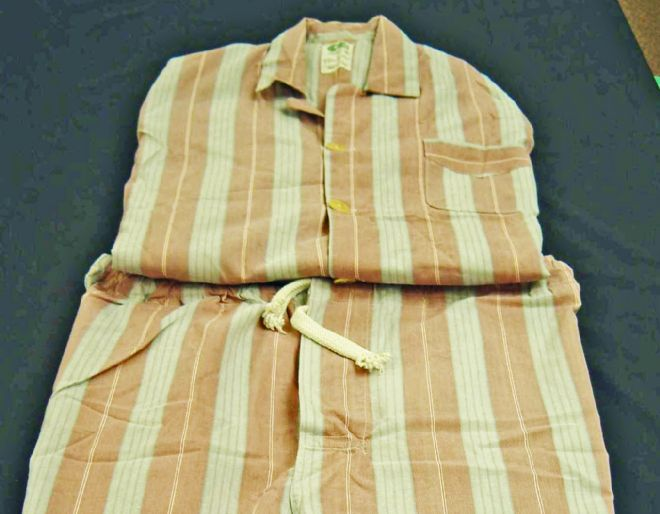 Folded pair of men's pyjamas with peach and white stripes