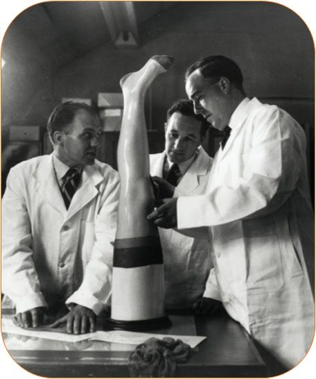 Three men in lab coats test a stocking for size on a plastic leg