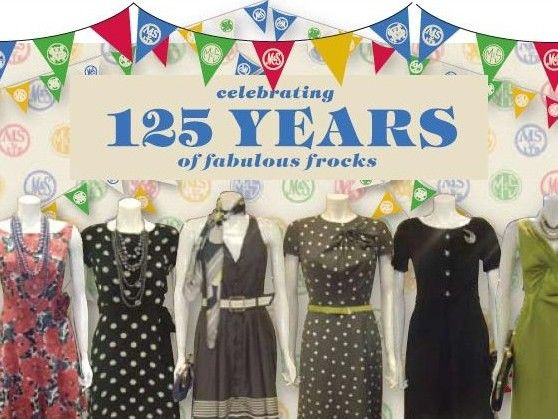 Window display with decorative bunting and mannequins wearing dresses