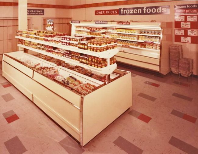 A freezer unit inside a supermarket with convenience food in tins and packets next to it