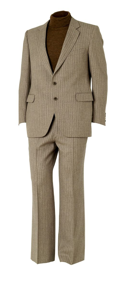 Mannequin wearing a grey two piece suit with a brown polo neck jumper underneath