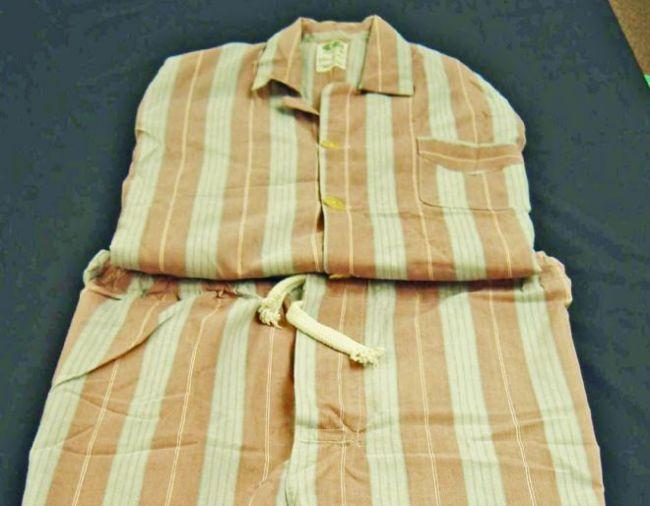 A folded set of pyjamas with peach and white stripes