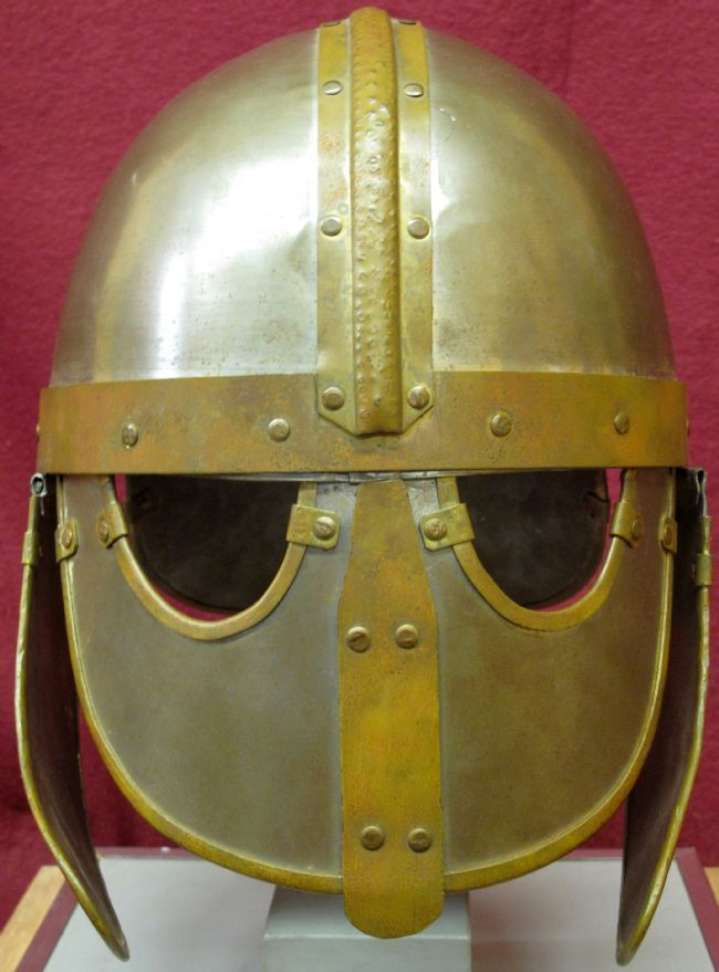 Helmet is made from a silver metal with gold coloured strips over the middle of the skull and across over the eyes.  The top half of the face is covered with metal and holes are cut for the eyes.  Metal flaps at the side protect the ears and side of the head