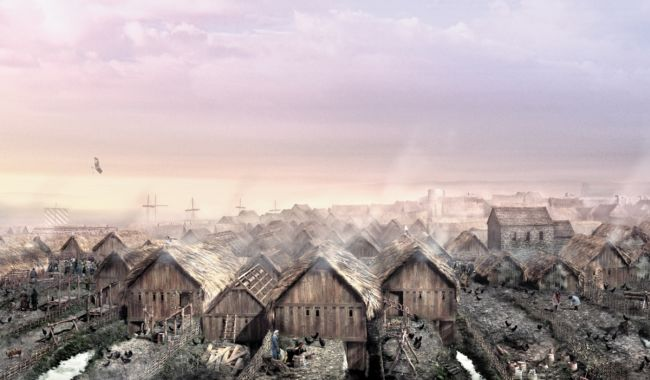 Wooden houses with  thatched roofs, built closely together.  Smoke is coming from the houses.