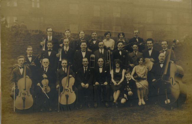 A photo showing the Huddersfield Labour Party Band from the 1920s.  They are mostly men with only a few women.  They are dressed in suits and dresses and hold their instruments.