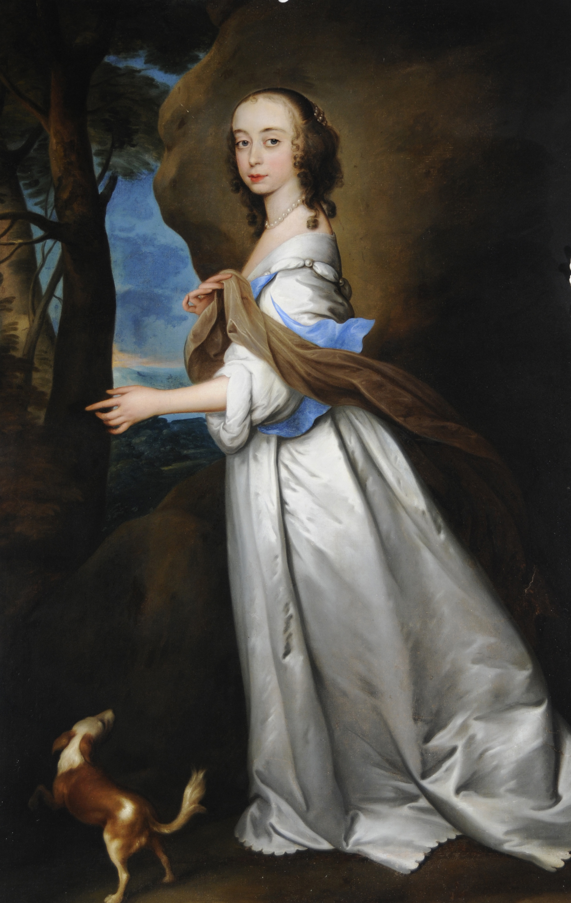 Portrait painting of Mary Ingram.  She has been painted on a walk outside, is wearing a white dress and has a small dog at her feet.