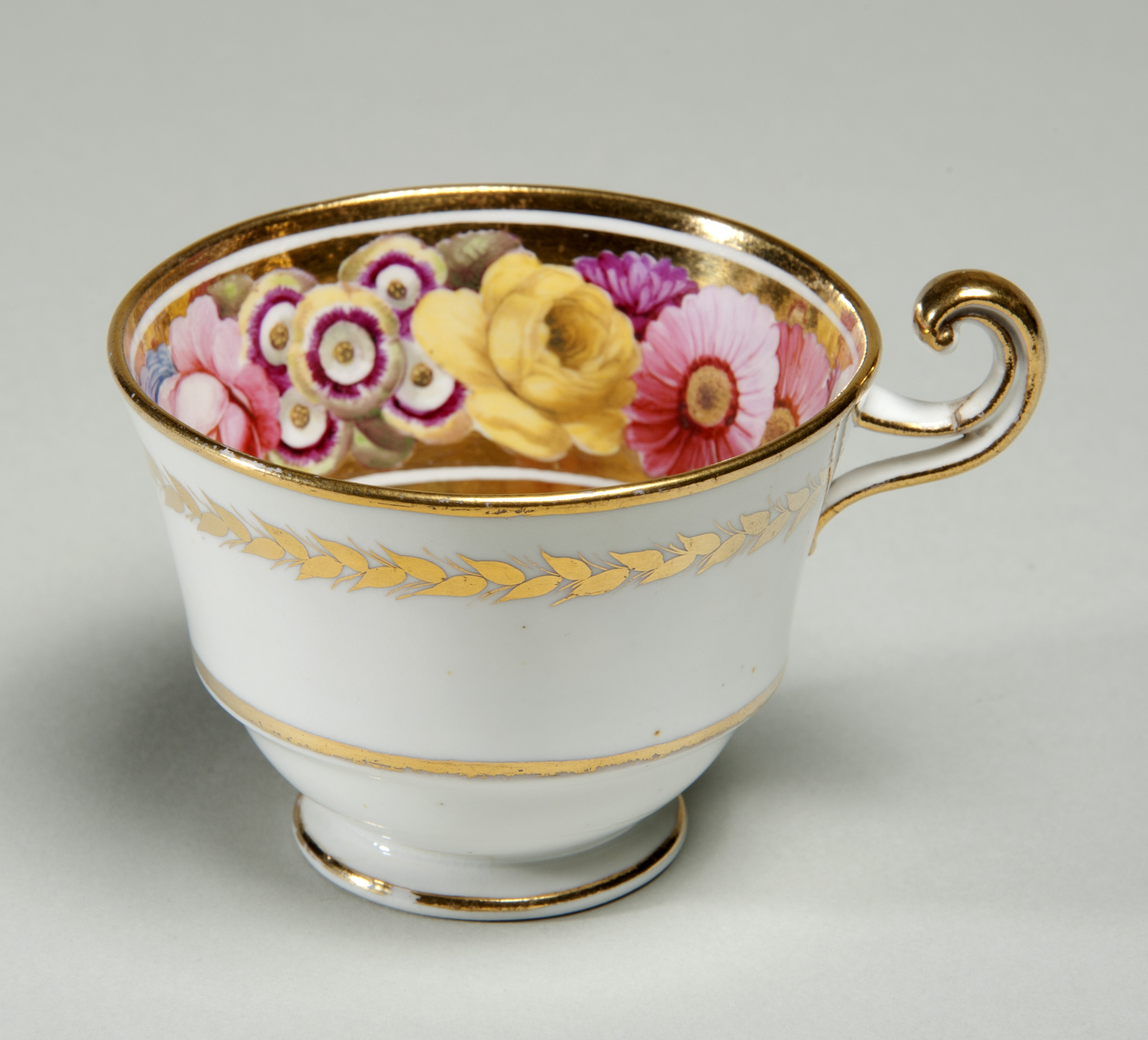 Colour photograph of a delicate looking teacup with pink and yellow flowers painted inside.  It has gold edges