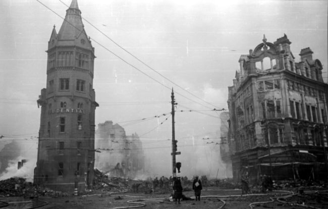 Black and White Photograph of a bombed street with a tower on the left and tall building on the right