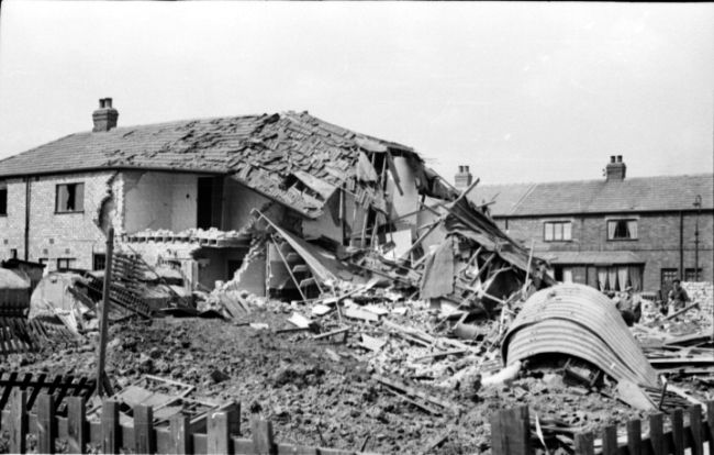 Bombed air raid shelter in Kathleen Road, Hull.  Some of a row of terraced houses have been destroyed and the air raid shelter is also damaged.