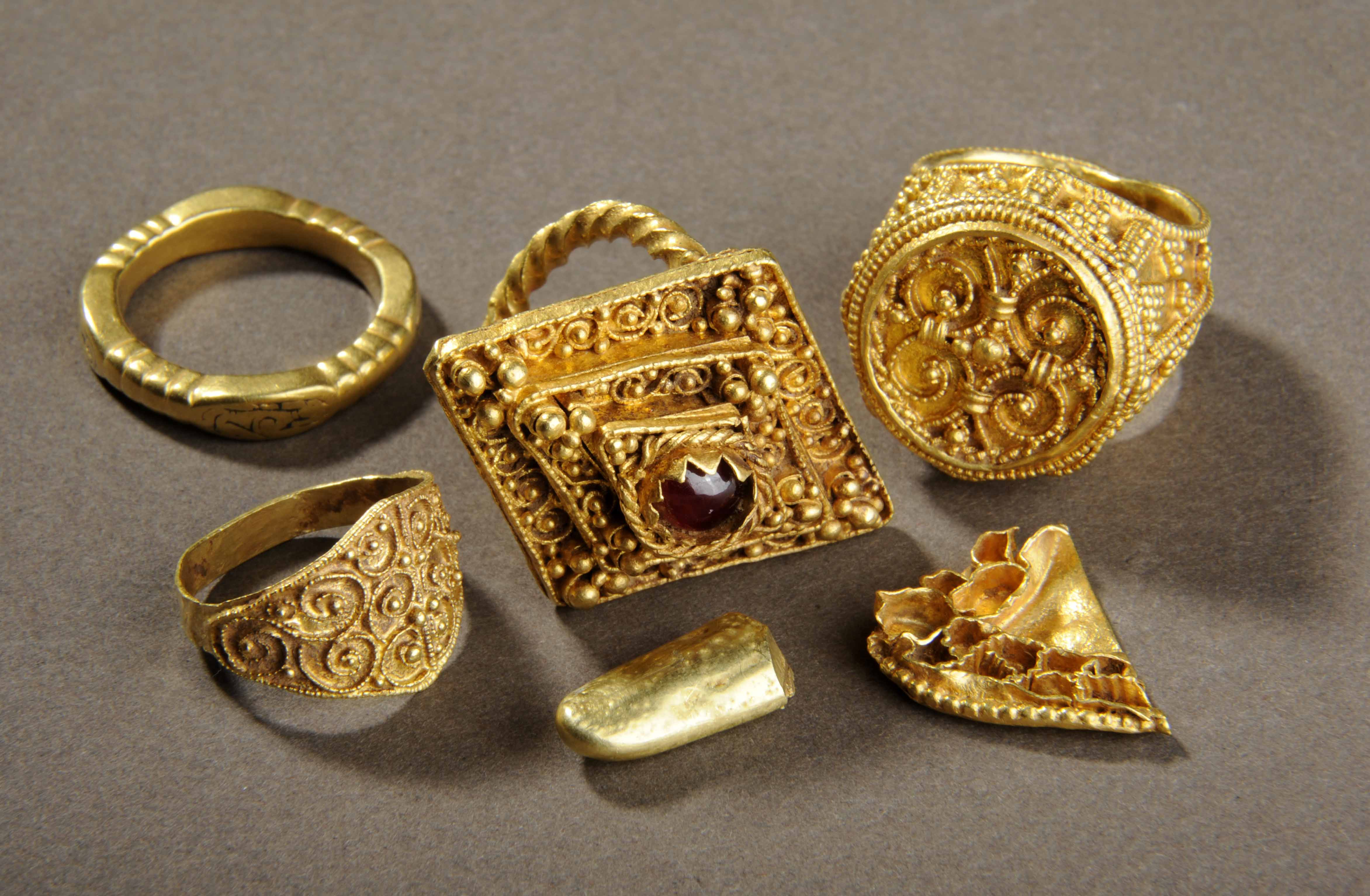 Four gold rings, a fragment of a brooch, a piece of gold ingot and a lead spindle whorl