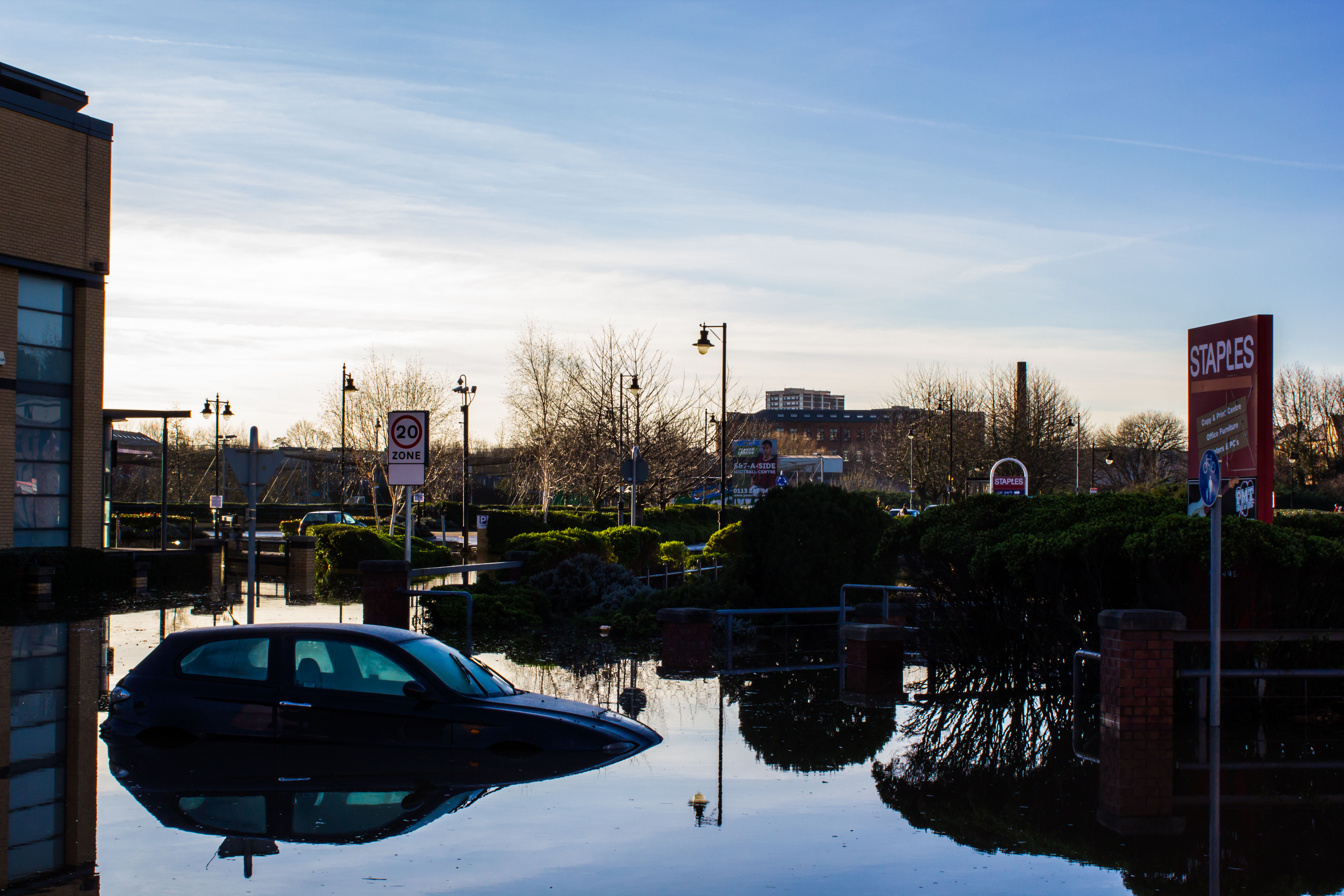 Photograph showing  a half submerged car in a shoppers car park.  The water has come over the top of the car bonnet.